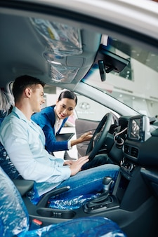 Menadżer dealera udziela uśmiechniętemu klientowi wskazówek dotyczących jazdy próbnej