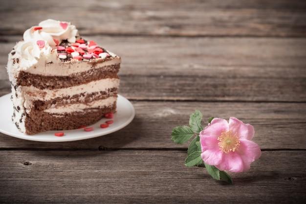 Menchii róża i tort na drewnianym tle