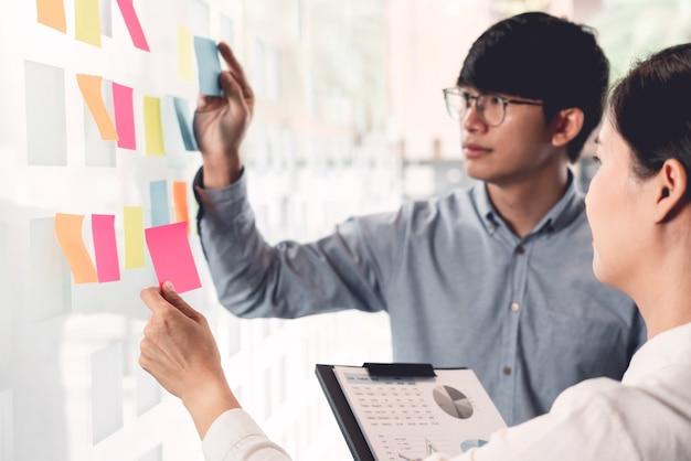 Menedżer biznesowy pokazujący pomysł na swój zespół i przyklejający do pracy wiele dokumentów na szklanym oknie