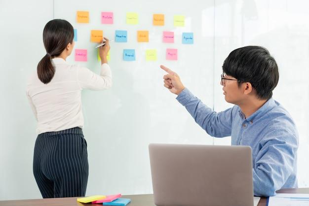 Menedżer biznesowy pokazujący pomysł na swój zespół i przyklejający wiele kartek notatek do szklanego okna, aby odnieść sukces w pracy w biurze kreatywnym spotkania biznesowego, koncepcji planowania i zarządzania.