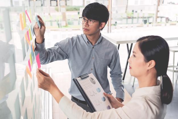 Menedżer biznesowy pokazujący pomysł na swój zespół i przyklejający wiele notatek na szklanym oknie