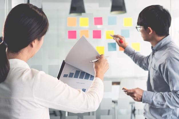 Menedżer biznesowy pokazujący pomysł na swój zespół i przyklejający wiele notatek na szybę