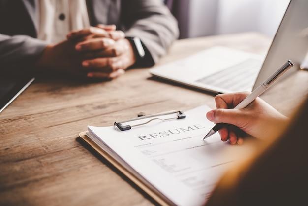 Menedżer ds. zasobów ludzkich wyjaśnia pracę osobie poszukującej pracy przed wypełnieniem cv na formularzu zgłoszeniowym, aby rozważyć przyjęcie do pracy w firmie.