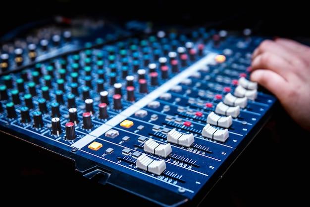 Menedżer dźwięku pracuje nad mikserem audio, przygotowuje nowy miks utworu lub pracuje nad wydarzeniem na żywo
