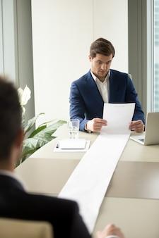 Menedżer hr czytający zbyt długo kandydaci wznawiają pracę