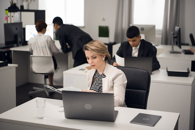 Menedżer jest zajęty pracą biurową przy biurku w biurze typu open space dużej firmy.