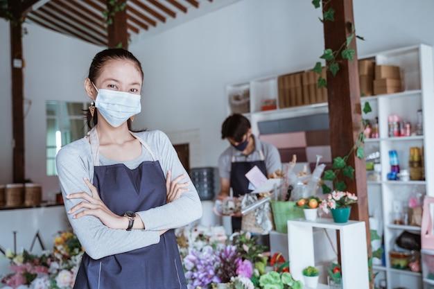 Menedżer kobieta noszenie maski na twarz kwiaciarnia stojąca skrzyżowane ramię ze swoim personelem