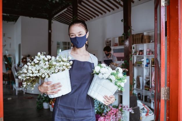Menedżer kobieta noszenie maski na twarz kwiaciarnia stojąca trzymając kwiat wiadro ze swoim personelem