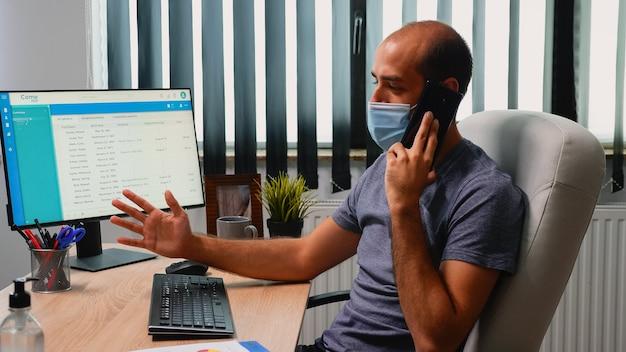 Menedżer nosi maskę wyjaśniając rozwiązanie problemu telefonu, siedząc na biurku w pokoju biurowym. freelancer pracujący w nowym, normalnym miejscu pracy, rozmawiający na smartfonie ze zdalnymi kolegami przed komputerem