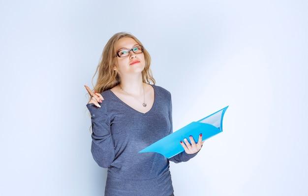 Menedżer otwierający i sprawdzający raporty w niebieskim folderze.