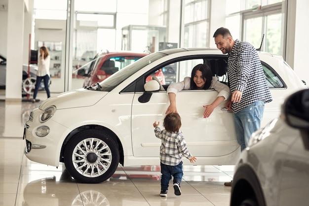 Menedżer pomaga młodej rodzinie wybrać najwygodniejszy samochód do miasta.