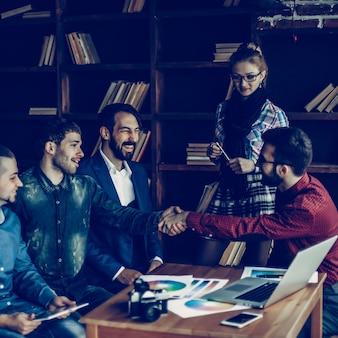 Menedżer reklamy z uściskiem dłoni wita klienta w nowoczesnym biurze