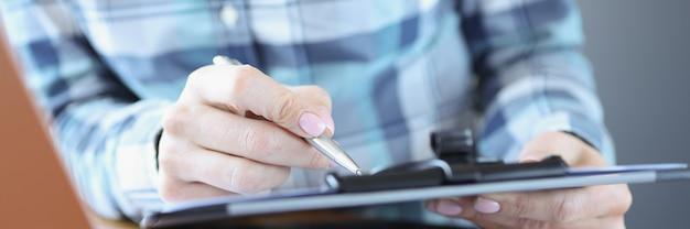 Menedżer siedzi przy biurku i trzyma dokumenty z koncepcją planowania strategii biznesowej pióra