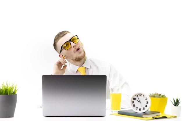 Menedżer słucha muzyki w słuchawkach i śpiewa akcent na żółtym soku z krawatem