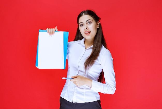 Menedżer trzymający niebieską teczkę i pokazujący na niej błędy.
