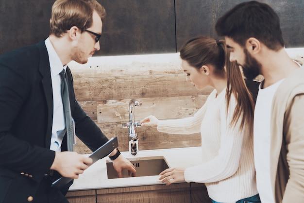 Menedżer w garniturze pokazuje zlew kuchenny dla ludzi.