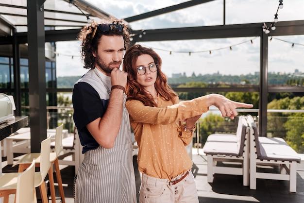 Menedżer w okularach. rudowłosa menadżerka w okularach stoi obok jej kręconego mężczyzny planującego otwarcie nowego tarasu