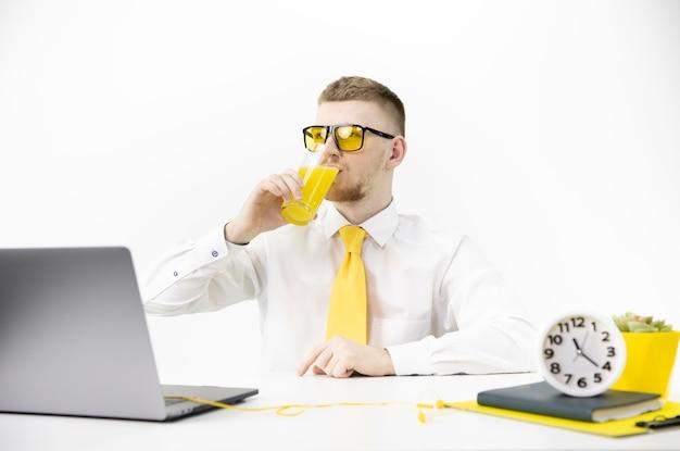 Menedżer w żółtych szklankach z laptopem pije sok, akcent na żółtym garnku