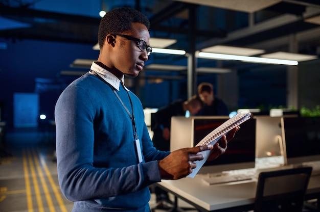 Menedżer wygląda w notesie, nocny styl życia w biurze. mężczyzna na stole, ciemne wnętrze centrum biznesowego, nowoczesne miejsce pracy