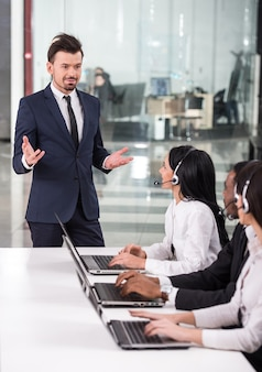 Menedżer wyjaśnia coś pracownikom call center.