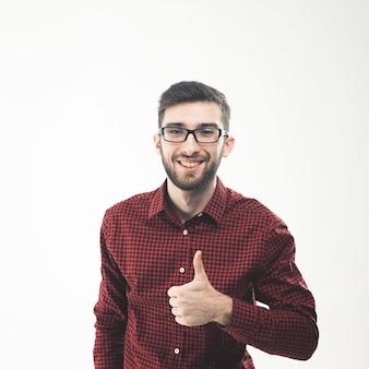 Menedżer wykonujący gest kciukiem w górę przy białej ścianie. zdjęcie ma puste miejsce na tekst
