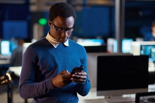 Menedżer z telefonem, biurowy styl życia. mężczyzna przy stole, ciemne wnętrze centrum biznesowego, nowoczesne miejsce pracy