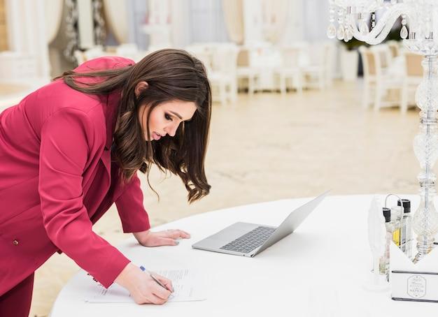 Menedżer zdarzeń pisze na papierze w sali bankietowej