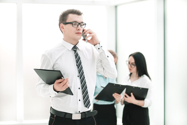 Menedżer ze schowkiem rozmawia przez telefon komórkowy w holu biura. pomysł na biznes