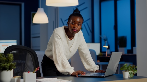 Menedżerka czarna kobieta stojąca przy biurku, szukająca na laptopie pisania na klawiaturze i wyglądająca na zmęczoną w kamerę