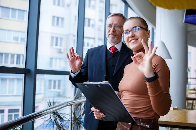 Menedżerka we własnym biurze opowiada udany nowy biznesplan dotyczący rozwoju gospodarczego swojemu szefowi-nauczycielowi-mentorowi. w rękach trzyma teczkę z ważnymi dokumentami.