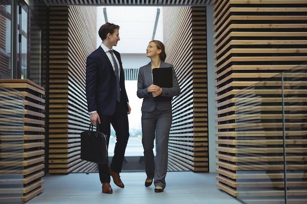 Menedżerowie biznesowi chodzą po korytarzu