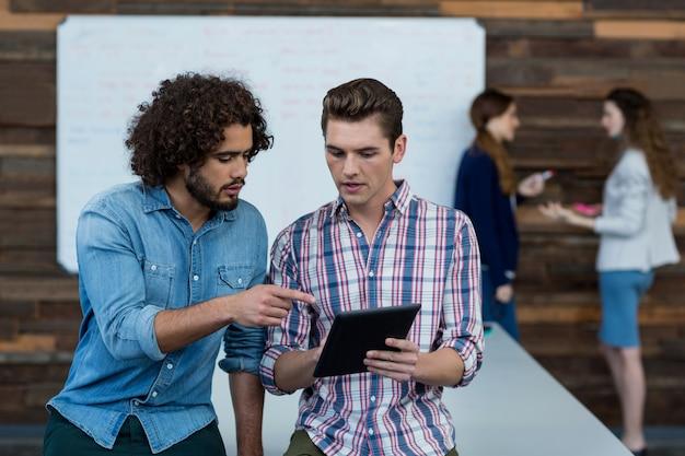 Menedżerowie biznesowi dyskutują na cyfrowym tablecie