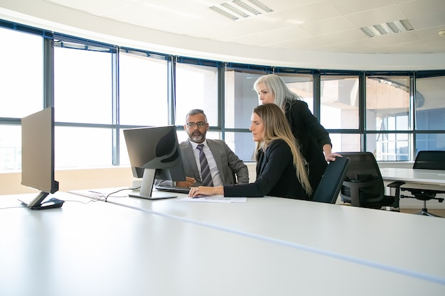 Menedżerowie firm omawiają rozwiązanie. biznesmeni gromadzą się w sali konferencyjnej, razem oglądając zawartość na monitorze komputera. koncepcja komunikacji biznesowej lub pracy zespołowej