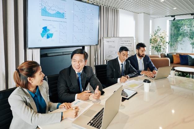 Menedżerowie firm spotykający się przy dużym biurowym stole i omawiający plany rozwoju firmy w czasie kryzysu gospodarczego spowodowanego pandemią covid-19