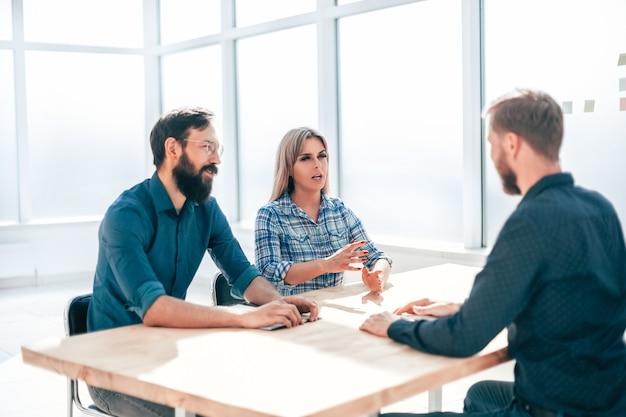 Menedżerowie i poszukujący pracy siedzący przy stole podczas rozmowy kwalifikacyjnej. pojęcie zatrudnienia