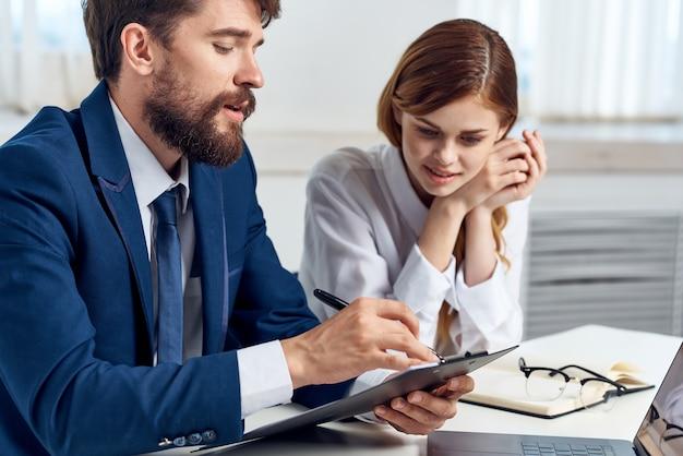 Menedżerowie mężczyzna i kobieta siedzący przy stole przed laptopem