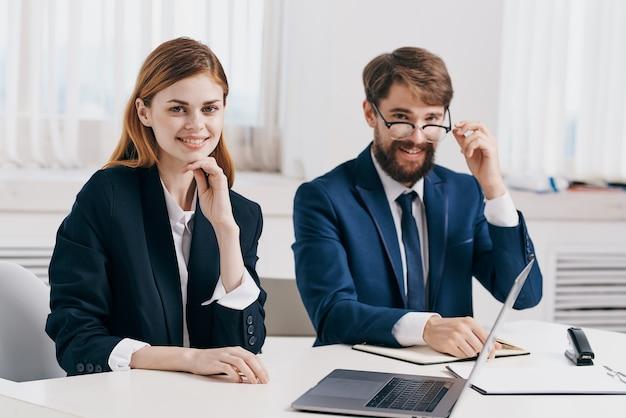 Menedżerowie mężczyzna i kobieta siedzący przy stole przed technologią profesjonalistów od laptopów