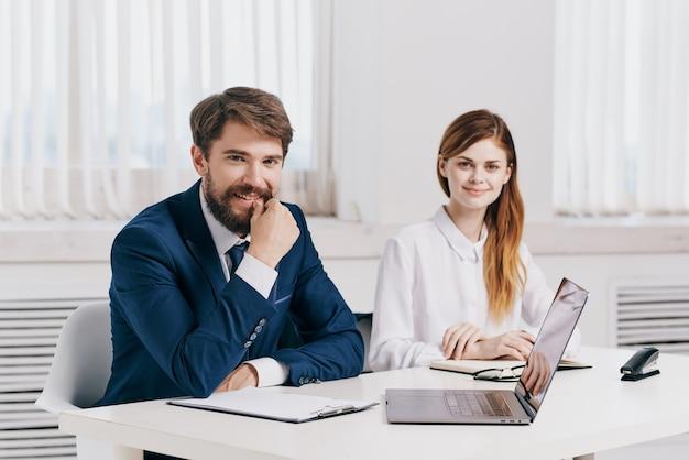 Menedżerowie mężczyzna i kobieta siedzący przy stole przed technologią zespołu laptopów