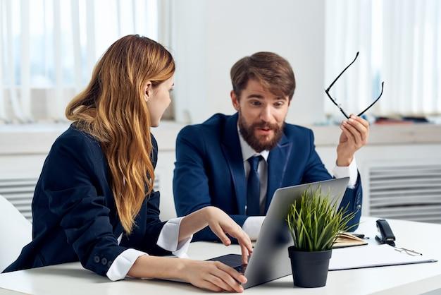 Menedżerowie mężczyzny i kobiety rozmawiają przy stole przed technologią zespołu laptopów