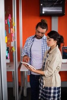 Menedżerowie płci męskiej i żeńskiej rozmawiają na cyfrowym tablecie