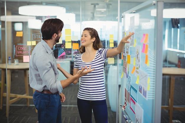 Menedżerowie płci męskiej i żeńskiej rozmawiają na tablicy