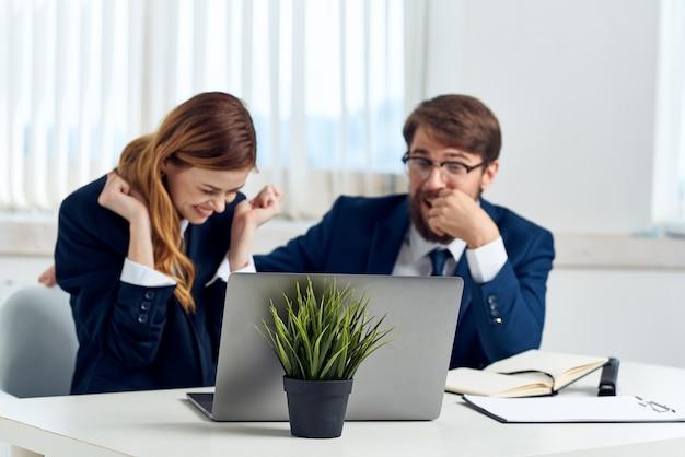 Menedżerowie rozmawiający w biurze przed urzędnikami w laptopie