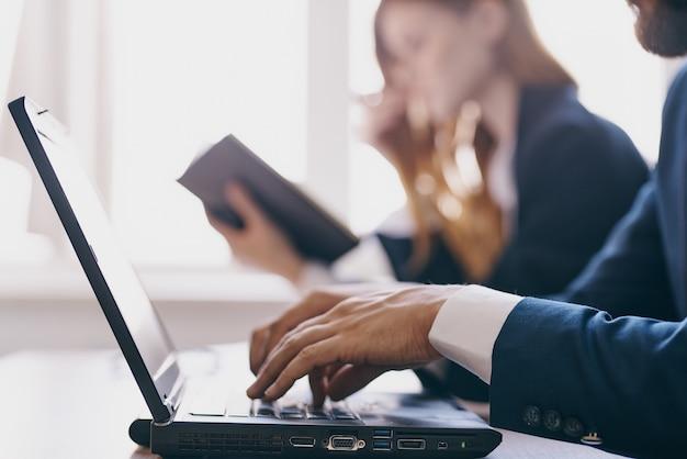 Menedżerowie siedzący przy biurku z laptopem komunikacja finansiści