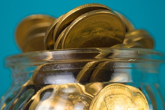 Menniczy pieniądze w szklanym słoju na stole z zielenią