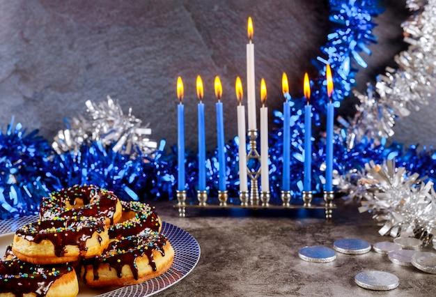 Menora chanuka, pączki, monety czekoladowe i dekoracje