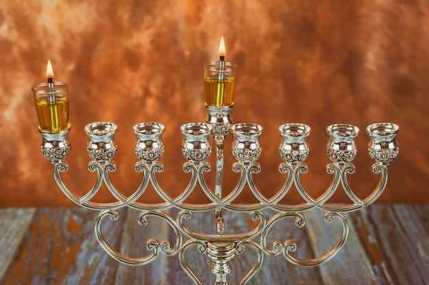 Menora tradycyjne żydowskie święto zapalające pierwszą świecę na hanukkahof płonącą świecę chanuka menora
