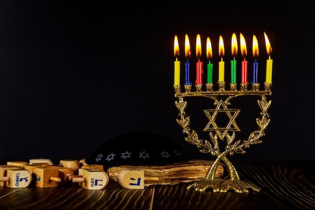 Menora z kolorowymi płonącymi świecami i dreidel