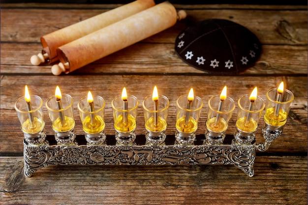 Menora z palącymi się świecami oliwnymi i jarmułką z totą na chanukę. święto żydowskie.