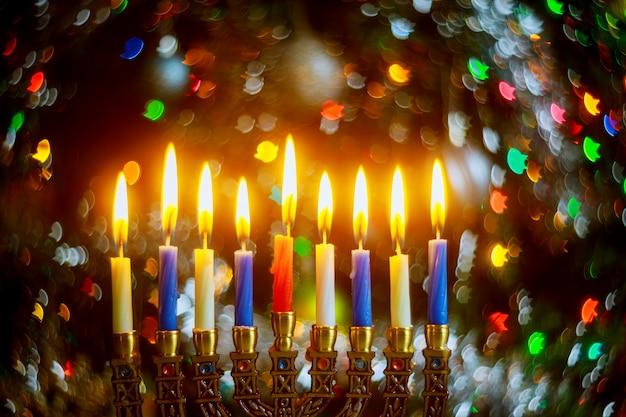 Menora z płonącymi świecami dla chanuki na błyszczącej powierzchni z rozmytymi światłami żydowskie święto