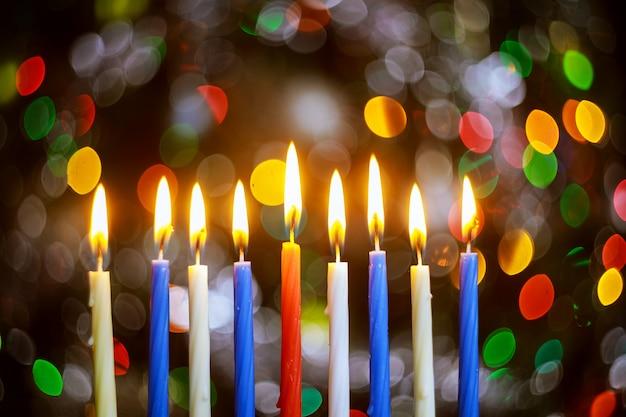 Menora z płonącymi świecami dla chanuki na błyszczącej powierzchni z rozmytymi światłami